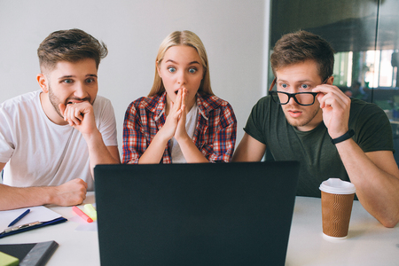 Worried young people sit together in room and look at laptop screen. Guy on left and young woman keep hands close to mouth. Another man hold glasses.
