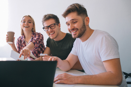 Cheerful and positive young coworkers laughing. They sit at table in white room. People look at laptop screen. Young woman hold cup of coffee and point.