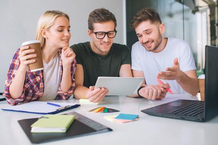Jóvenes felices y alegres trabajan juntos en una mesa. Chico en camisa negra mantenga tableta. Lo miran todos juntos. La gente está interesada.