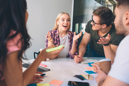 Cheerful young blonde woman smile and look forward. She wave with hands. Brunette woman and two young men look at her. They listen to. People work together in coworking