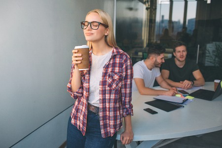 Smart young blonde woman wear glasses. She stand and hold cup of coffee. She enjoyes. Two young men sit behind her and work. They talk between themselves.
