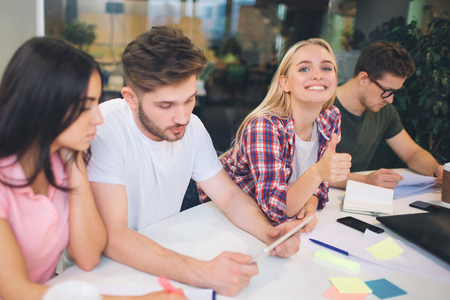 Picture of cheerful young blonde woman look on camer and smile. Other students work on their projects at table. They are serious and concentrated.