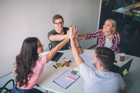 Happy and cheerful young people sit around table and keep hands together. They look happy and joyful. People play as team in room.