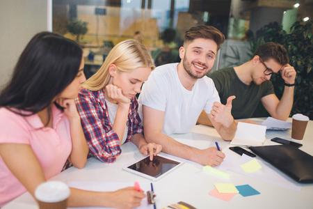 ハンサムな若いあごひげの男は、彼の同僚の間に座って、大きな親指を持っています。彼はカメラに微笑む。他の人は働いて下を向きます。彼らは 写真素材