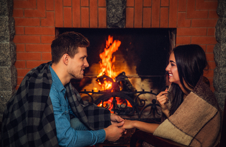 Cozy picture of lovely young man and woman look at each other and smile. They have blankets on shoulders. Young couple sit at fireplace with fire.