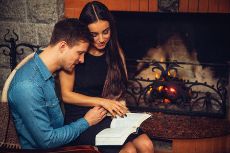 Serious and concentrated young man and woman sit together at fireplace. They read opened book. Model touch page with hand. 写真素材