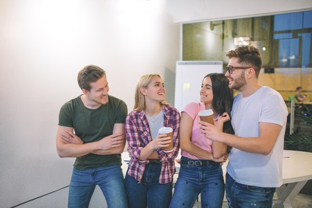 Cheerful and positive young men and women stand together. They look at each other and laugh. Positive people hold cups of coffee. They are in one room.