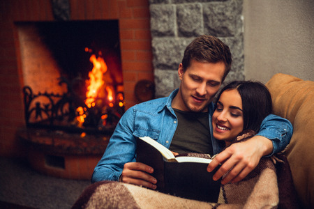 Positive and cheerful couple sit together. Young woman covered with blanket. Guy read book for her. They sit near fireplace.