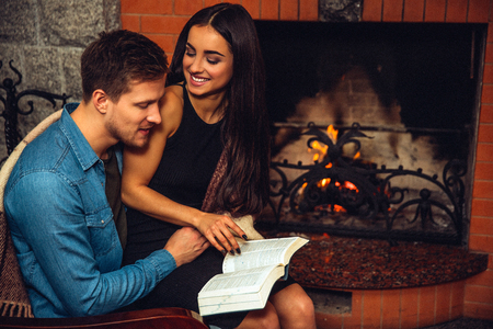 Cheerful young women sit on mans lap and look at heim. She smiles and hold book opened. Guy look at it. Model turning page. They sit at fireplace.