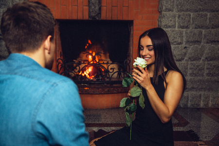 Lovely young woman smell white rose. She hold it close to face and look at it Guy sit with back to camera. They are near fireplace. 写真素材