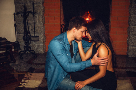 Tender and romantic picture of young couple sitting together at fireplace. They touch their foreheads and look in eyes. Guy hold hand on her forearm.