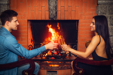 Beautiful couple sit at fireplace and touch glasses with champaigne. They look at each other. Couple have date. They sit at fireplace. Stok Fotoğraf
