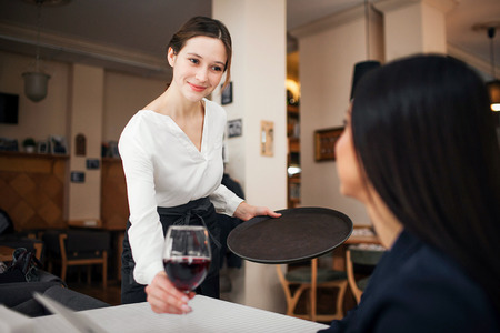 Cheerful and polite young waitress look at customer and smile. She put glass of wine on table. Female customer sit at table and smile to waitress Banco de Imagens