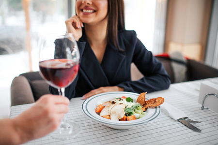 Cheerful young businesswoman sit at table and smile. Waitress put glass of red wine on table. Bowl with salad already stand there 免版税图像