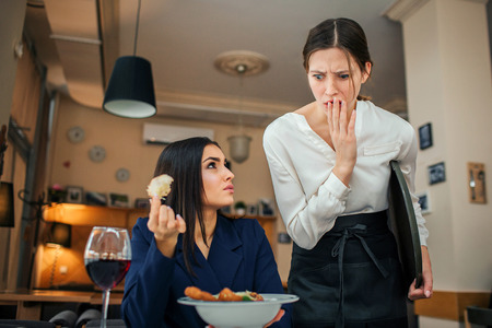 Amazed waitress look at salad bowl and cover mouth with hand. Young businesswoman sit at table and look at her. She angry and mad. Customer hold piece of food