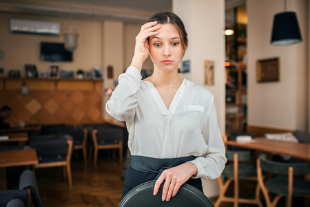 Frustrated young waitress look down. She hold tray in left hand. Right one hold on forehead. Young woman stand alone in restaurant