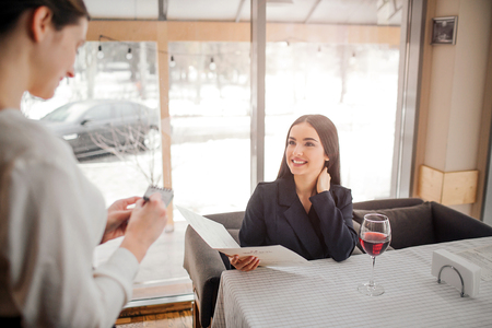 Cheerful young businesswoman sit at table and give order to waitress. They both smile. Waitress writing in notebook. Young woman has glass of wine at table 写真素材