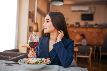 Beautiful young woman sit at table and look to left. She hold glass of red wine and touch her hair. Salad bown stand in front of her. Phone lying besides Banque d'images