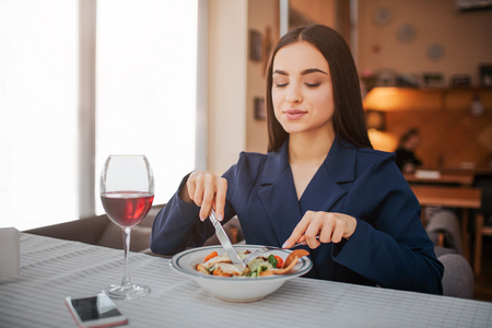 Proud and nice young woman sit at table and eat salad with fork and knife. She look down. Glass of red wine stand besides. Phone lying on table Imagens
