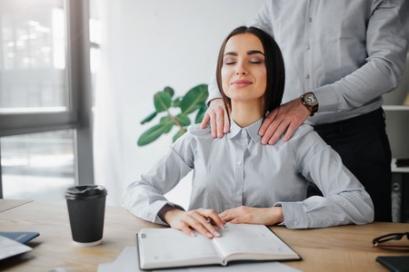 Young woman get attention from boss. He does shoulder massage for her. She is relaxed and pleased. Young woman sit in room at table. Guy stand behind her. Stockfoto