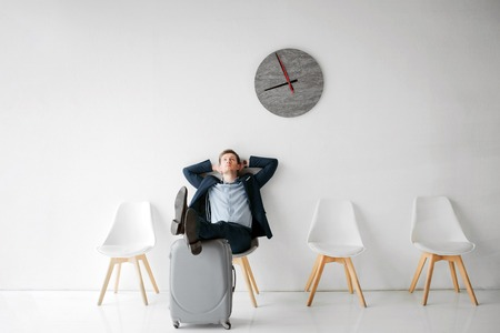 Relaxed young man sit on white chair in room alone. He wait for flight. Guy hold legs on suitcase. Young man lean to wall.