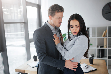 Concept harassment. Quiet and silent young brunette look down. She hold hands on mann chest. She doesnt want intimate relationships with him. Guy embrace brunette.