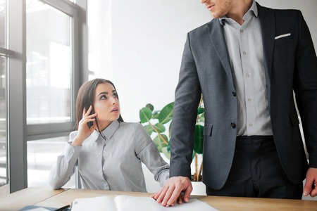 Concept harassment. Scared young woman sit at table and look at her boss. She is scared. Guy hold his hand on top of her. He wants sex with her Stock Photo