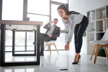 Concept harassment. Sexy young woman bend down to take pen from floor. She looks lovely. Her boss sit at table on chair and look at her butt. He is sexually excited