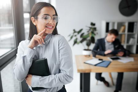 Une jeune femme joyeuse et positive se tient debout et sourit. Elle touche ses cheveux et regarde le patron. Il est assis à table. Guy regarde brune. Banque d'images