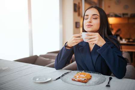 Young woman enjoying her cup of coffee. She sit at table and smell it. Model has cake on plate on table. Reklamní fotografie