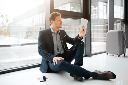 Busy young man sit on floor and talk on facetime. He hold tablet in front of himself and look at screen. Young man left phone aside and suitcase behind.