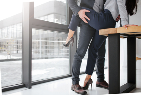 Cut view of man in suit stand and hold womans leg in sexual pose. She sit on table. They are in room close to window.