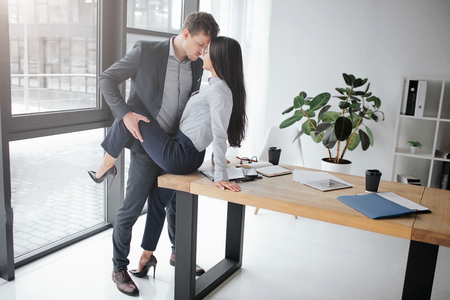 Sexual and intimate picture of couple at work. She sit on table. He hold her leg in pose. They keep faces close to each other.