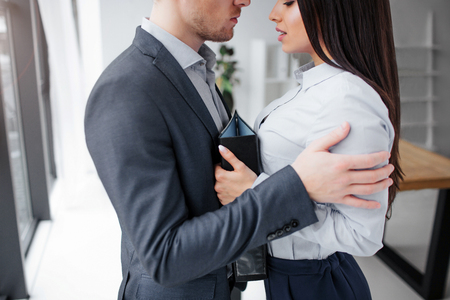Cut view of young man and woman standing very close to each other. He embrace her. She looks down and hold black folder. They stand in office. Stock Photo