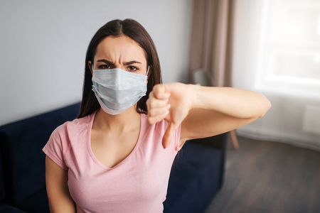 Negative young woman look on camera and show big thumb down. She sit in room alone. Model is angry and serious. Her mouth covered with protection mask. She is sick.