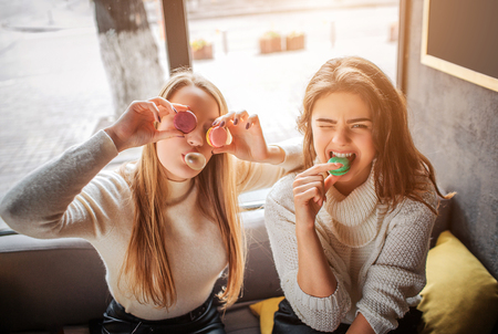 Funny young women cover eyes with macarons. They pose on camera. Brunette bites piece of macarone. They have fun
