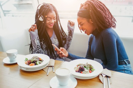 Happy and positive young african women have fun. First model listen to music. Second smiles. They have lunch at table in cafe