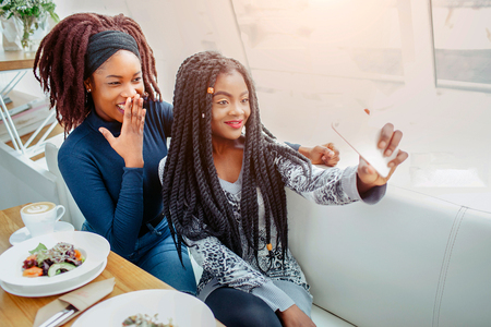 Cheerful nice young african women in cafe. They take selfie on phone camera. Models smile. They sit at table