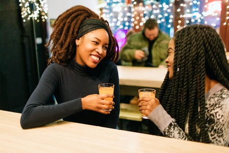 Two young african women sit in cafe. They have conversation. Model smile. They hold glasses of orange juice