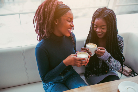 Attractive african women smile. They sit in cafe and hold cups of coffee. Second model looks down