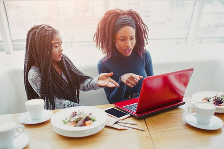 Young african american women sit at table. They point at laptop. Models are frustrated and amazed. They have food and drink on table