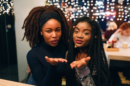 Attractive and beautiful african models look straight and send kisses. They smile and sit together. Young women looks lovely 写真素材