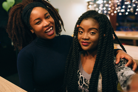 Two young african models look straight and pose. They smile and sit together in cafe 写真素材
