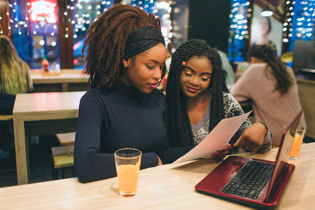 Nice young african woman study in cafe. They sit and look at piece of paper. Models smile. They have red laptop on table
