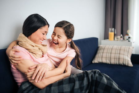 Happy and positive young woman sit together with her daughter on couch in room. They laugh out loud. Young woman is sick. Her throat is wrapped with scarf. Girl embrace mother.