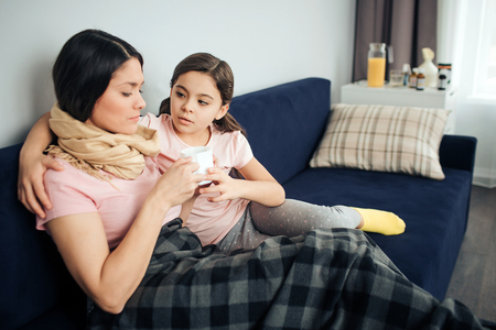 Sick youbng woman sit on couch with her daughter. She hold white cup in hands and look at it. Child embrace mother and look at her. She worry.