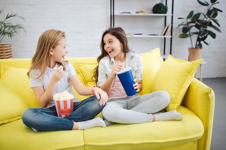 Deux adolescents heureux et joyeux sont assis sur un canapé jaune. Ils se regardent et sourient. Les filles ont un bol de pop-corn et une tasse de coca.