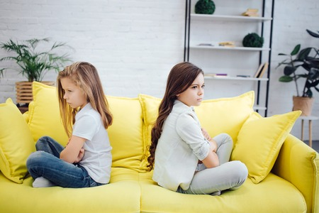 Angry and mad girls sit on yellow sofa in room. They dont look at each other. Girls are very upset.
