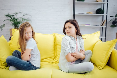 Upset and angry girls sit on yellow sofa and look at eah other. They hold hands crossed. Teenagers have a quarrel between them. Stock Photo - 115899146