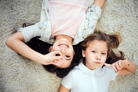 Deux jeunes adolescents s'amusant ensemble. Ils sont allongés sur le tapis tête à tête. Les filles regardent la caméra et font des grimaces. Isolé sur fond gris. Banque d'images